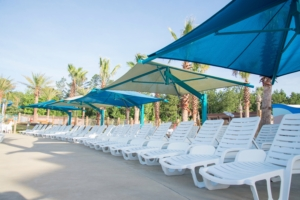 Image of poolside lounge chairs covered by shade structures